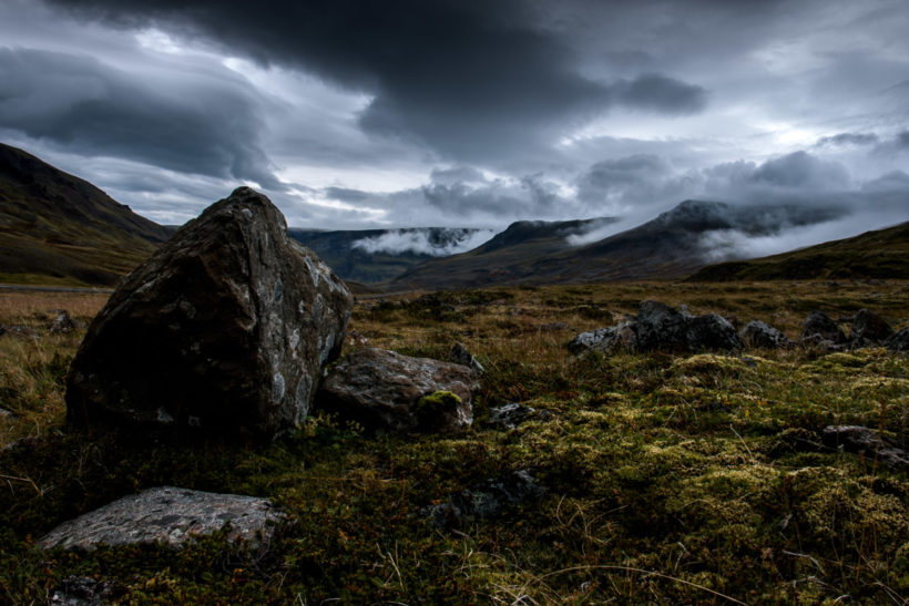 Dramatic landscape strewn with boulders in a misty mountain pass during a summer road trip, Westfjords, Iceland