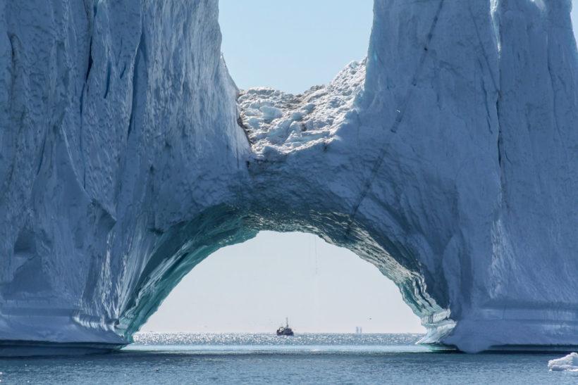 Arch-shaped iceberg with a fishing vessel in the distance, Ilulissat Kangerlua, Kalaallit Nunaat (Greenland)