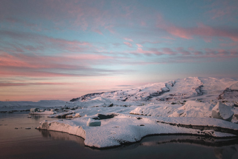 Pink light of dawn hitting off the snowy mountains and ice at at Jokulsarlon glacier lagoon, Iceland